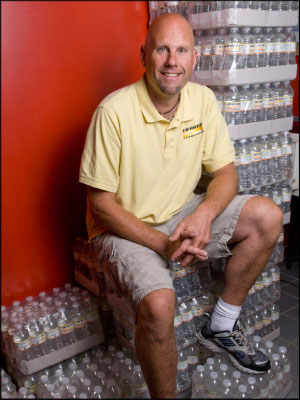 THIRST QUENCHER: Troy Minske, owner of Rum River Automotive, has donated thousands of bottles of water branded with his shop's logo to area organizations. Photo by Andy Shelter