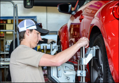 OFFERING OPPORTUNITY: Intern Lawson Butler performs a variety of jobs during his two weeks, including fixing flat tires and replacing rotors. Here, he sets an alignment target.